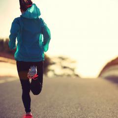 This is an image of a woman in exercise clothes running down an empty road