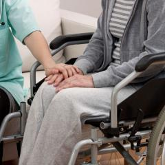 This is an image of a person in medical scrubs holding the hand of another person in a wheelchair