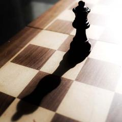 Queen chess piece casting long shadow.