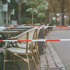 empty outdoor dining separated by caution tape