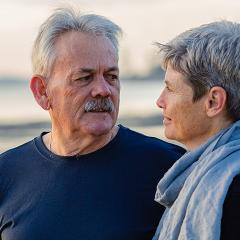 An older man and woman on a beach.