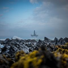 An isolated oil rig at sea off a rocky coastline