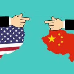 America and China represented as flags in the geographical shape of their countries, pointing at one another.