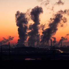 skyline of an industrial area at dusk, with pollution billowing into the sky.