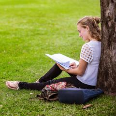 Kate Green sitting under a tree reading a book at UQ